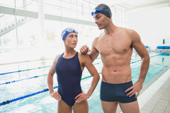 Fit couple swimmers by pool at leisure center. Portrait of a fit male and female swimmers by the pool at leisure center Stock Images