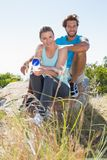 Fit couple taking a break at summit smiling at camera Royalty Free Stock Photography