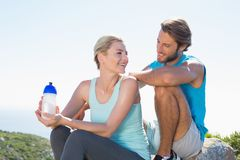 Fit couple taking a break at summit smiling at each other Royalty Free Stock Images