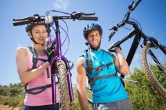 Fit couple walking down trail smiling at camera holding mountain bikes Stock Photo