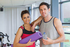 Fit couple with water bottle and exercise mat in exercise room Stock Image