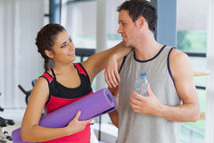 Fit couple with water bottle and exercise mat in exercise room Stock Photos