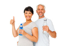 Fit couple with water bottles gesturing thumbs up Stock Image