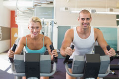 Fit couple working on exercise bikes at gym Stock Photos