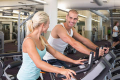 Fit couple working on exercise bikes at gym Stock Photo