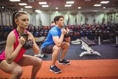 Fit couple working out in weights room Stock Image