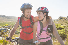 Fit cyclist couple smiling together on mountain trail Stock Photo