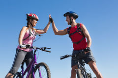 Fit cyclist couple standing at the summit high fiving. On a sunny day Royalty Free Stock Photography