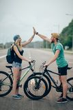 Happy biker couple giving high five while riding bicycle in countryside. Fit cyclist couple standing at the summit high fiving on a sunny day Royalty Free Stock Photo