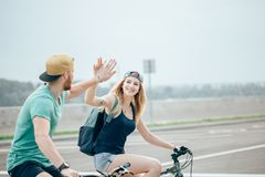 Happy biker couple giving high five while riding bicycle in countryside Royalty Free Stock Photography