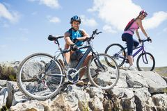 Fit cyclist couple taking a break on rocky peak smiling at camera Stock Image