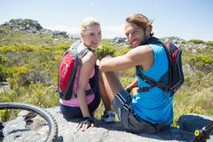 Fit cyclist couple taking a break on rocky peak smiling at camera Stock Images