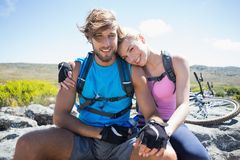 Fit cyclist couple taking a break on rocky peak smiling at camera Royalty Free Stock Image