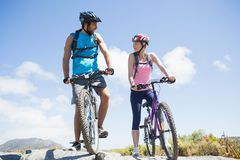 Fit cyclist couple taking a break on rocky peak smiling at each other Stock Photos