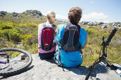 Fit cyclist couple taking a break on rocky peak Royalty Free Stock Photos