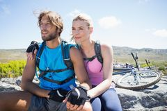 Fit cyclist couple taking a break on rocky peak Stock Images