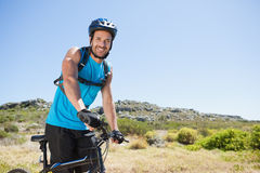 Fit cyclist riding in the countryside smiling at camera Stock Photos