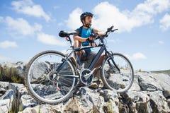 Fit cyclist taking a break on rocky peak Stock Photography