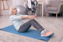 Fit elderly woman doing sit-ups at home. I love fitness. Charming elderly woman sitting on the yoga mat and doing sit-ups, trying to work out her abdominal Royalty Free Stock Photo