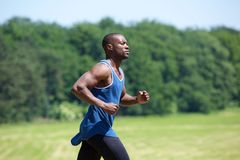 Fit exercising man running outside Stock Photos