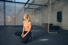 Fit female athlete at crossfit gym. Young woman kneeling on floor with kettle bell and looking away. Fit caucasian female athlete at crossfit gym relaxing after stock images