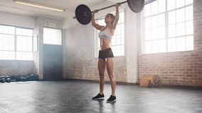 Fit female athlete doing heavy weight lifting. Full length image of strong young woman exercising with barbell. Fit female athlete lifting heavy weights Stock Photo