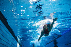 Fit female athlete swimming in pool royalty free stock photo