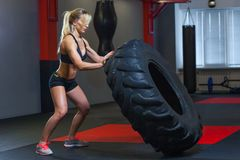 Fit female athlete working out with a huge tire, turning and carry in the gym. Crossfit woman exercising with big tire royalty free stock photos