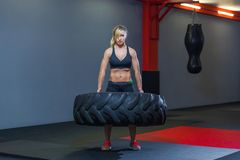 Fit female athlete working out with a huge tire, turning and carry in the gym. Crossfit woman exercising with big tire stock photo
