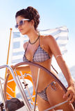 Fit female behind wheel of sailboat Royalty Free Stock Photo