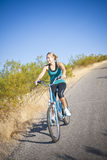 Fit Female on a Bike Ride. An attractive fit female exercising on a morning bike ride. Lots of copy space above Royalty Free Stock Photos