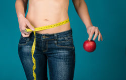 Fit female body with apple and measuring tape. Healthy fitness and eating, diet lifestyle concept. Royalty Free Stock Photography