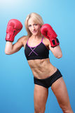 Fit female boxer. On a blue background with a smile on her face Royalty Free Stock Images