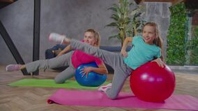 Fit female and child exercising with fitness ball