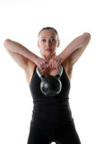 Fit female doing an upright row with a kettlebell. Image of a fitness model using a kettlebell to work her shoulders Royalty Free Stock Images
