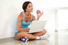 Fit female holding food and using her computer Royalty Free Stock Image