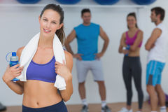 Fit female holding water bottle with fitness class in background Stock Photos