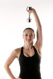 Fit female holding a weight above her head. Image of a fitness model using a dumbbell to work her shoulders Stock Photo