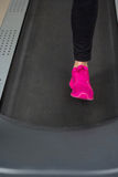Fit female legs on a treadmill at the gym Royalty Free Stock Photos