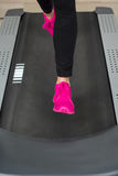 Fit female legs on a treadmill at the gym Royalty Free Stock Images