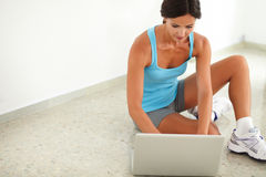Fit female sitting while surfing the web Stock Images