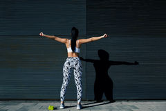 Fit female in sportswear exercising on black background outdoors Stock Photos