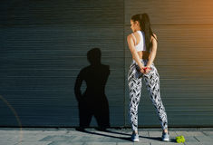 Fit female in sportswear resting after training on black background outdoors Stock Photography