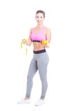 Fit female standing holding fruits and tape line Royalty Free Stock Photography