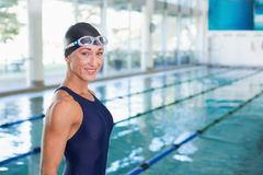 Fit female swimmer by pool at leisure center Stock Images