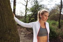 Fit female taking a break after running on forest trail. Pretty young woman wearing headphones listing to music and looking away Royalty Free Stock Photo