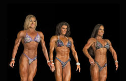 Fit Figure Triad. Three gorgeous and fit figure contestants made a powerful impression in the figure competition at the 2015 NPC Universe Championships in Royalty Free Stock Images