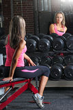 Fit fitness girl looking into the mirror at the gym. Image of a cute female after a workout Royalty Free Stock Image