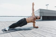 Fit fitness man doing fitness exercises outdoors at city. Fit fitness man doing fitness exercises outdoor at city background. He doing hamstring leg exercise and stock photography