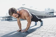 Fit fitness man doing fitness exercises outdoors at city royalty free stock photos